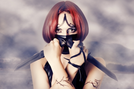 Fantasy style - red haired woman with dark creative make up, mask on her face and two combat knifes Stock Photo - 14587891