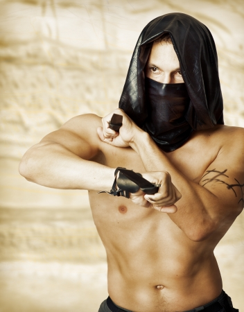 terror: Man assassin with sexy torso in black mask and hood holding two knifes in hands Stock Photo