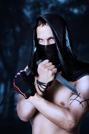 Man assassin with sexy torso in black mask and hood holding two knifes in hands Stock Photo