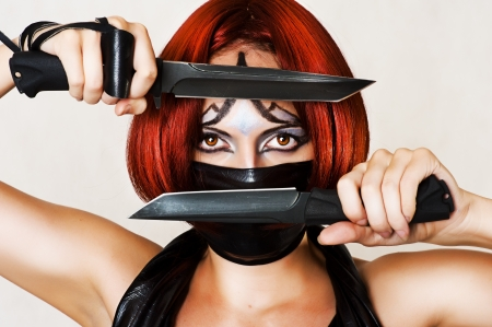 Fantasy style - red haired woman with dark creative make up, mask on her face and two combat knifes Stock Photo - 14692471