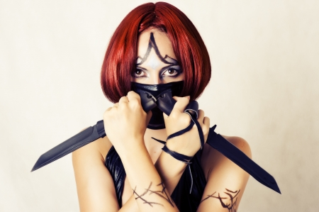 Fantasy style - red haired woman with dark creative make up, mask on her face and two combat knifes Stock Photo - 14692470