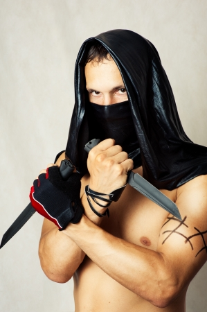 Man assassin with sexy torso in black mask and hood holding two knifes in hands photo