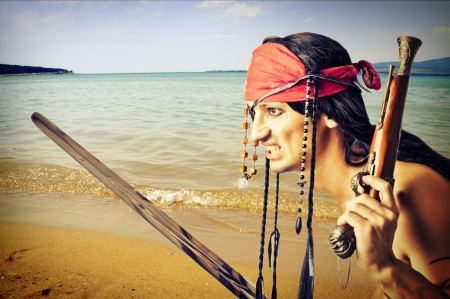 Handsome pirate with hand gun and medieval sword on a seaside of island Stock Photo - 14715581