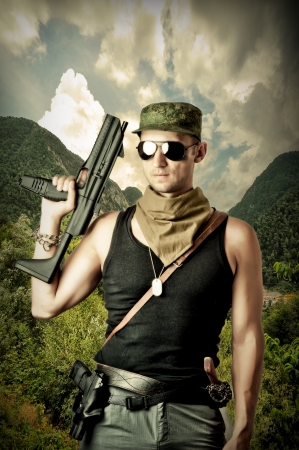 man holding gun: Handsome dangerous military man holding automatic and gun wearing fashion sun glasses Stock Photo