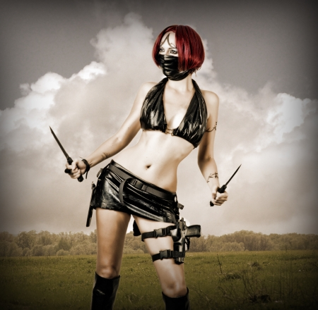 Sexy dangerous woman in black mask with two hunting knifes Stock Photo - 14715578