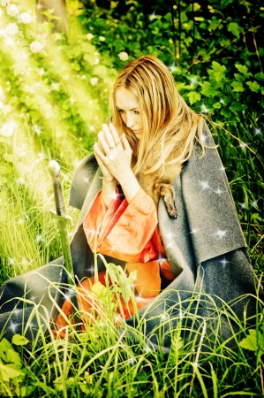 young girl on her knees praying in woods in front of the medieval sword. The divine light from above Stock Photo - 14715588