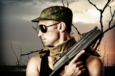 Handsome dangerous military man holding automatic and gun wearing fashion sun glasses and cap photo