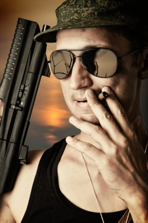 sexy military man wearing fashionable sunglasses and cap with automatic smoking a cigar  photo
