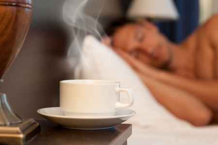 hotel stay: man sleeping on a bed, a cup of hot steaming coffee on the bedside table and lamp