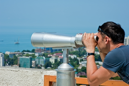 man on vacation looking through binoculars at the seascape photo