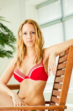 red bra: Young sexy woman in red swimsuit sitting on wooden chair on tropical resort