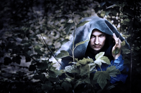 Mystery man in a raincoat with a hood hiding in the trees Stock Photo