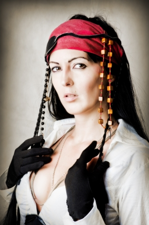 Fashion portrait of woman pirate in black gloves, red bandana and white sexy blouse photo