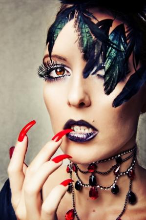 uñas largas: Retrato de la moda sexy mujer vampiro gótico con maquillaje y uñas largas rojas Foto de archivo