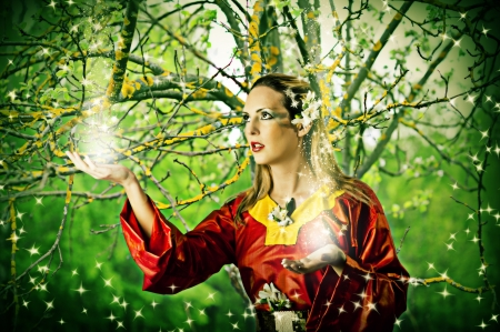 Young beautiful woman fairy in summer magic forest photo