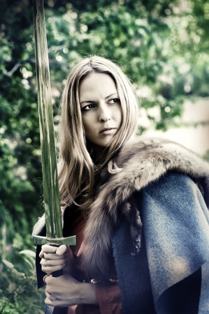 Beautiful blond sexy woman warrior with sword outdoor
