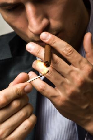 hombre fumando puro: retrato de joven fumando cigarro confidente hombre Foto de archivo