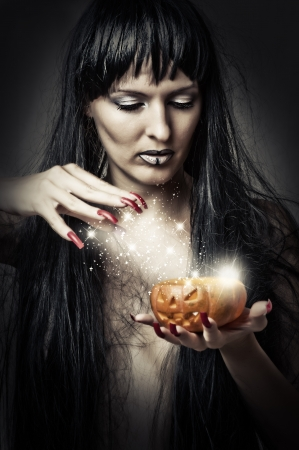 Sexy brunette woman witch making magic to pumpkin Stock Photo - 14980587