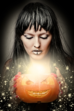 Sexy brunette woman witch making magic to pumpkin photo