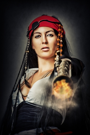 ancient sexy: Portrait of sexy female pirate shooting from an old pistol