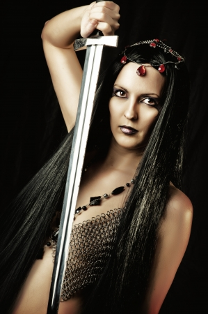 Fashion portrait of sexy eastern brunette woman with medieval sword photo