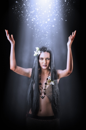 Beautiful asian brunette woman witch making magic photo