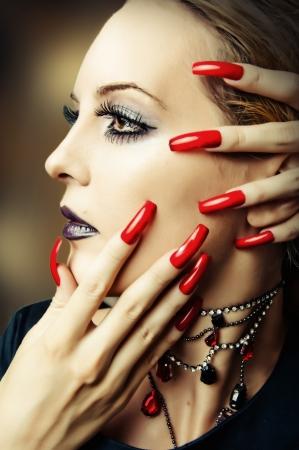 uñas largas: Cara de la mujer con la moda de maquillaje, pestañas postizas y largas uñas rojas Foto de archivo