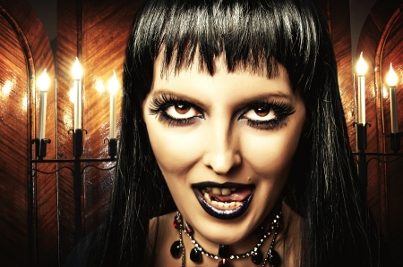 evil witch: Gothic brunette woman witch with dark make-up and evil eyes