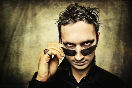 sole occhiali: Demone maschio con gli occhi cattivi e occhiali da sole Archivio Fotografico