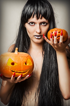Woman witch with black hair and two pumpkins
