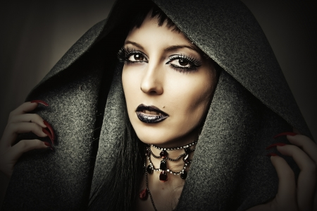 Young beautiful brunette woman in gray hood with fashion gothic make up and ancient necklace