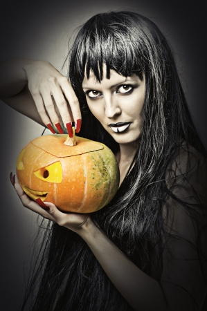Woman witch with black hair with pumpkin photo