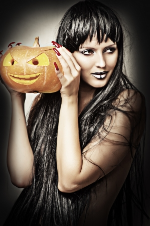 Woman witch with black hair with pumpkin