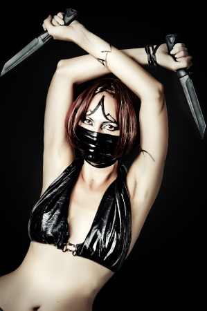 Sexy dangerous woman in black mask with two hunting knifes photo