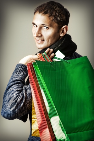 Fashion man holding shopping multicolored bags photo