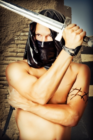 Man assassin with sexy torso in black mask and hood holding  knife and sword in hands photo