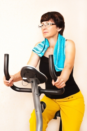 adult fitness woman work out on exercising bike at home photo
