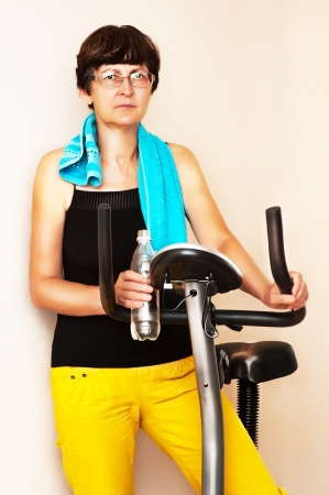adult fitness woman work out on exercising bike at home holding bottle of water in hand photo