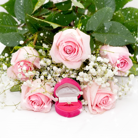 Close-up of tender pink roses with diamond ring in box on a white fabric photo