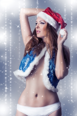 Sexy woman santa claus in white pants, vest with fur mink and red had photo