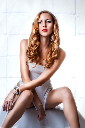 Young sexy beautiful woman in white lingerie, wearing wristwatch and bracelets photo