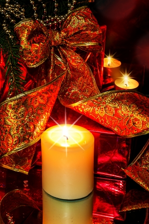 Night Christmas Decorations background - red ribbon; beads; tree candles on fir tree branch photo