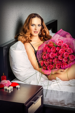 Romance. Beautiful young woman with a big bouquet of red roses photo