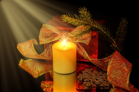 Christmas background. Decorations, candle and fir tree branch on black with light Stock Photo