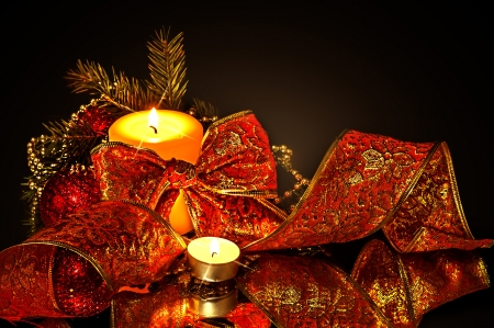 Christmas background. Decorations, candle and fir tree branch on black photo