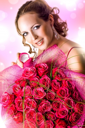Valentines Day. Marriage Proposal. Young woman holding box with ring and large bouquet of roses photo