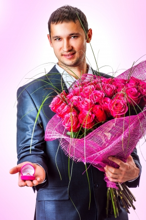 Valentines Man with flowers and ring un pink box. Proposal scene  photo