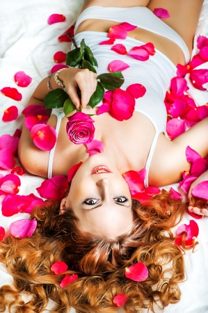 Romance. Beautiful young woman with curly hair in bed with a red rose and petals photo