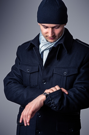 Casual. fashion portrait of sexy handsome man in black coat, hat and white scarf. View the time on a wristwatch photo