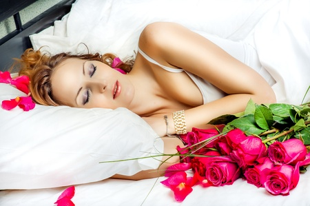 anniversary sexy: Romance. Beautiful slepping woman in white bed with red roses Stock Photo